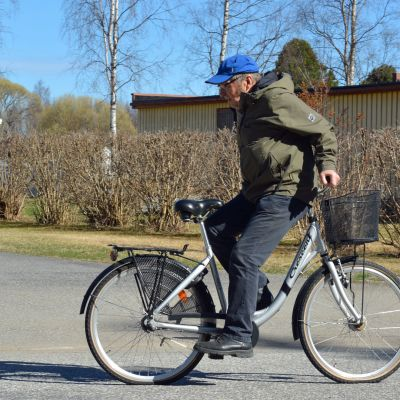 Mies ajaa polkupyörällä selkä menosuuntaan päin.