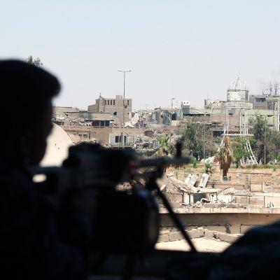 Konekiväärillä aseistautunut Irakin poliisijoukkojen jäsen vartiossa Mosulissa.