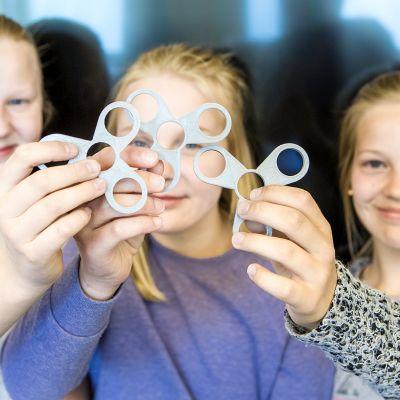 Tytöt pitävät käsissään itse 3D-tulostettuja fidget spinnereitä