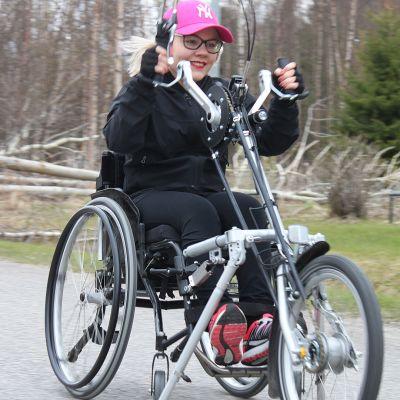 Elina Tytärniemi viilettää täyttä vauhtia pyörätuoliinsa kiinnitetyn käsipyörän avulla.