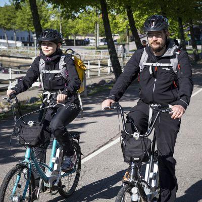 THL:n tutkijat Taina Siponen ja Pekka Taimisto pyöräilevät tutkimusreput selässään.