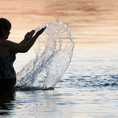 Nainen leikkii vedellä järvessä.