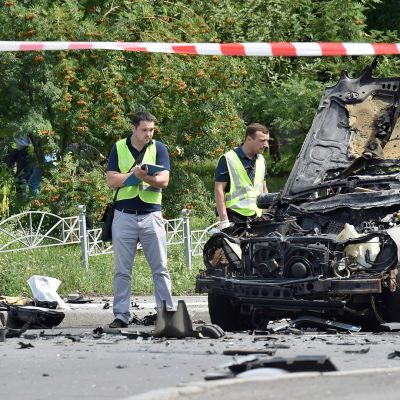 Poliisit tutkivat autopommin tuhomaa autoa.