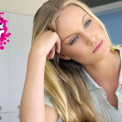 en ung kvinna som lutar sitt huvud på sin hand och ser orolig ut