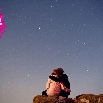 ett par som håller om varandra på en klippa och ser upp på stjärnhimmeln