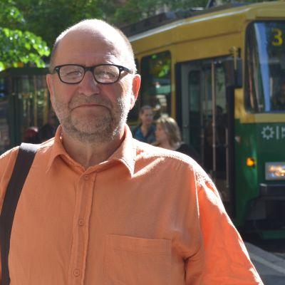 Utomhus tagen bild i halvfigur på en äldre man med glasögon som bär en blekorange skjorta, i bakgrunden syns spårvagn nummer tre och människor som går längs med gatan.