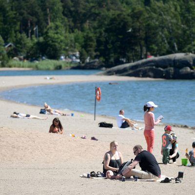 Ihmiset viettävät kesäpäivää uimarannalla.