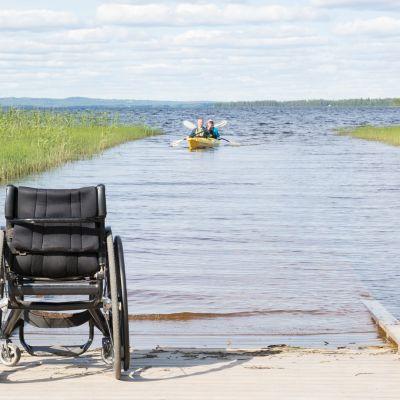 Pyörätuoli laiturilla ja ihmisiä melomassa.
