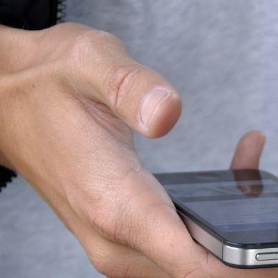 mies käyttää kännykkää