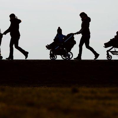 Äitejä ja lapsia ulkona kävelemässä.