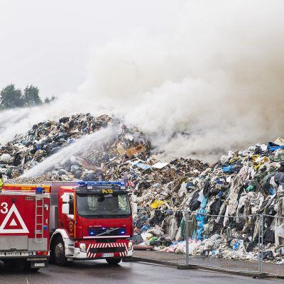 Palokunta sammuttaa tulipaloa jätevarastolla.