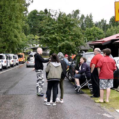 Paikallisia asukkaita ja poliisiautoja kadunvarressa Vantaan Hakunilassa.