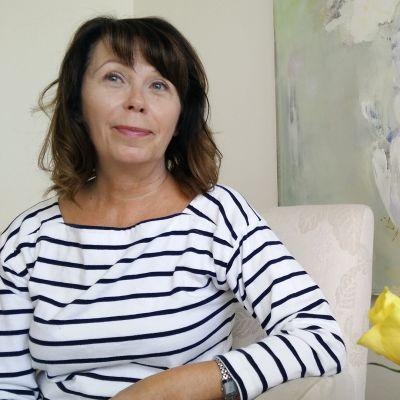 Psykologi Soili Poijula istuu taulun edessä, vieressä keltaisia ruusuja.