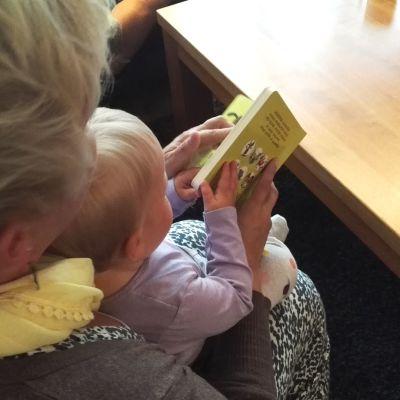Lapsi lukee kirjaa äitinsä sylissä.