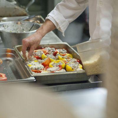 Mies valmistaa täytettyjä paprikoita ravintolan keittiössä.