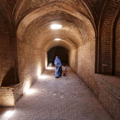 Afganistanilainen äiti kulkee lapsensa kanssa tiilikäytävässä Heratissa.