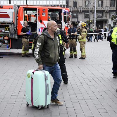 Matkustajia Helsingin rautatieaseman edessä matkalaukkuineen.