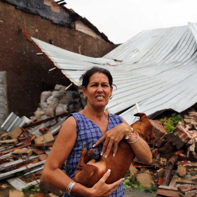 Nainen piteli koiraansa sylissään tuhoutuneen kotitalonsa edustalla Remedioksen kaupungissa Kuubassa 9. syyskuuta.