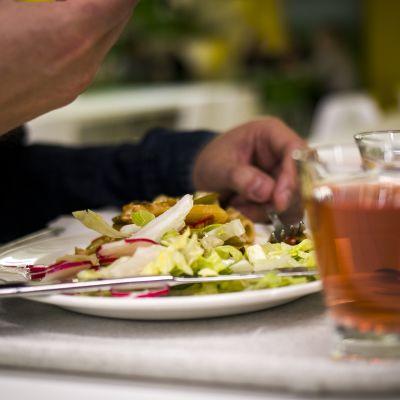 Opiskelija syö lounasta yliopiston ravintolassa.
