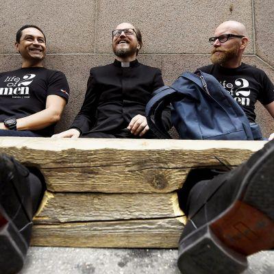Pastori Kai Sadinmaa istuu jalkapuussa vierellään vihkimänsä miespari Raul Medina ja Hannu Virtanen Helsingin hiippakunnan tuomiokapitulin edustalla.