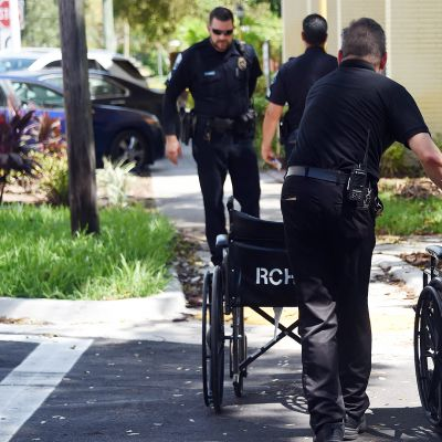 Poliisi siirtää kahta pyörätuolia hoitokodin edessä kadulla.