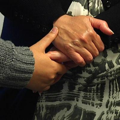 Två personer håller varandra i handen.
