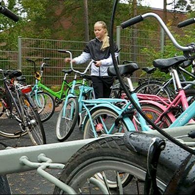 Tyttö taluttaa pyörää