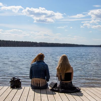 Kaksi nuorta naista istuu laiturilla järvellä keväällä.