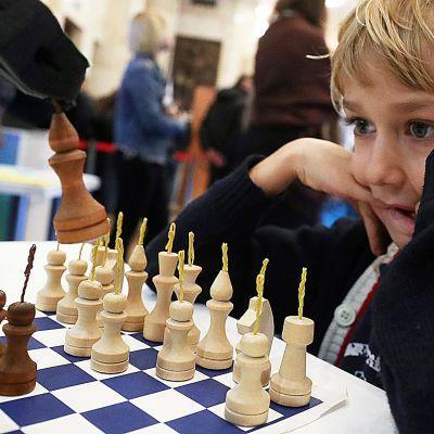Pieni poika pelaa shakkia robottia vastaan tiedemessuilla 6.10. Moskovassa.