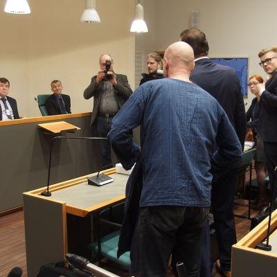 Syytetty asettelee takkiaan istuntosalissa oikeudenkäynnin alussa.