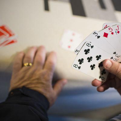 Pelikortteja kädessä.