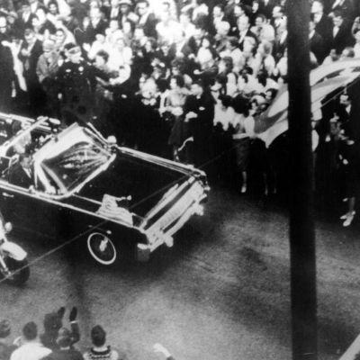John F. Kennedy matkustaa vaimonsa kanssa avoautossa Dallasissa marraskuussa 1963.