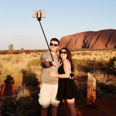 Turistipariskunta ottamassa selfietä Uluru-kiven luona.