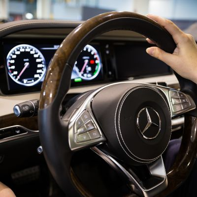 Lähikuva naisen käsistä auton ratissa.