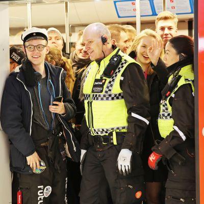 Matkustajia ja turvamiehiä metron ovella.