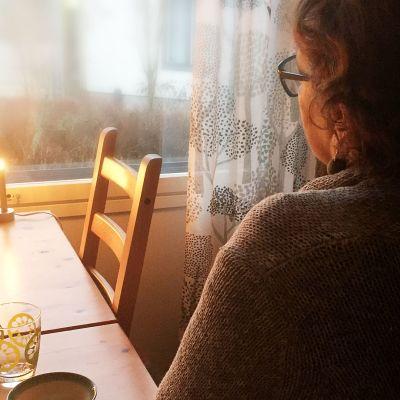 Nainen katselee ikkunasta ulos.