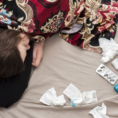Sairastava ihminen makaa sängyllä nenäliinojen, kuumemittarin ja lääkkeiden kanssa.