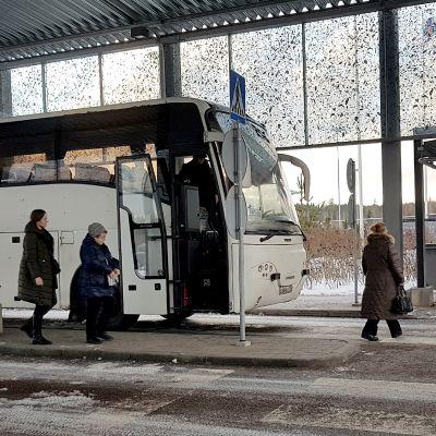 Venäläinen turistibussi Nuijamaan rajatarkastusasemalla menossa Lappeenrantaan. Matkustajat kävelevät kohti passintarkastusta.