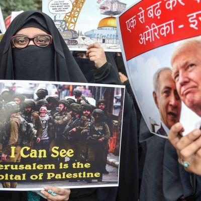 ihmiset pitelevät plakaateja mielenosoituksessa