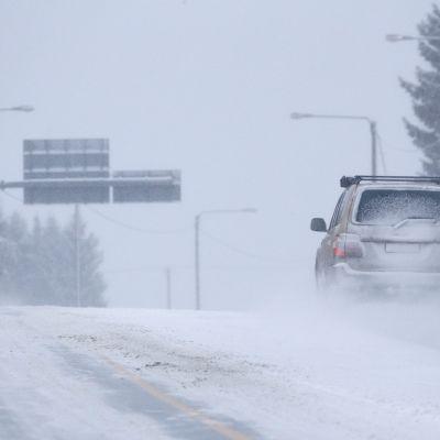 Autoja liikenteessä lumisessa säässä.