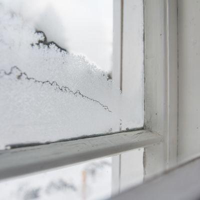 Vanhan rakennuksen ikkuna on jäässä.