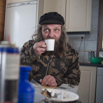 Mies juo kahvia.