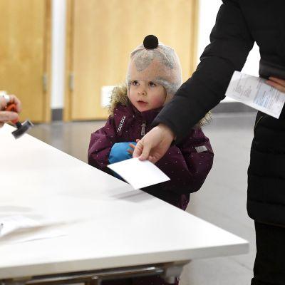 Äänestäjä leimauttaa äänestyslipukkeensa vaalipäivänä Kulosaaren ala-asteella Helsingissä sunnuntaina.