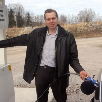 Kuvassa mies tankkaamassa autoa