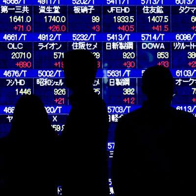 Henkilöiden silhuetteja pörssikursseja näyttävän taulun edessä.