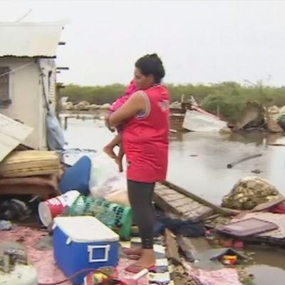 Tongalainen nainen lapsi sylissä katselee tuhoja.
