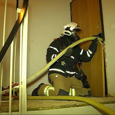 Palomies työntää vesiletkua kerrostaloasunnon oven läpi