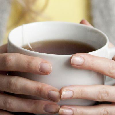 Teekuppi naisen käsissä.