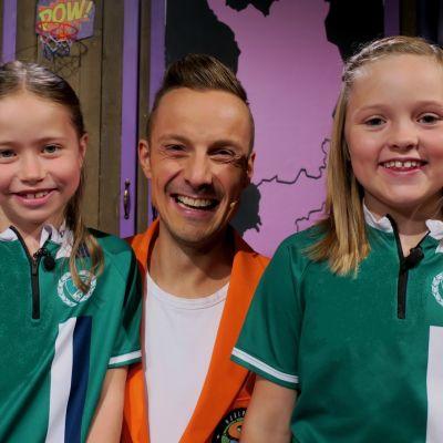Superhjälparnas programledare Jontti Granbacka poserar tillsammans med två flickor som besöker tv-studion