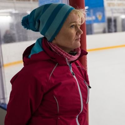Nainen talvitamineissa katselee jäähallin jääkentälle.
